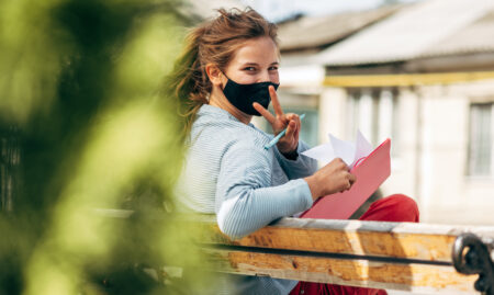 women on an outdoor bench wearing covid mask looking back at camera